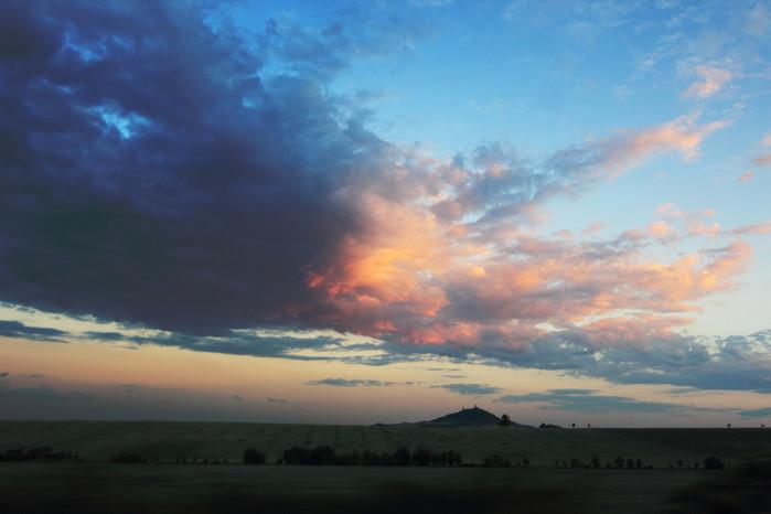 Hrad Házmburk snasvícenou oblačností zapadajícím Sluncem - autor: